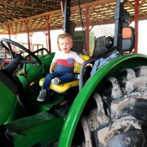 Young grandson sitting on a tractor